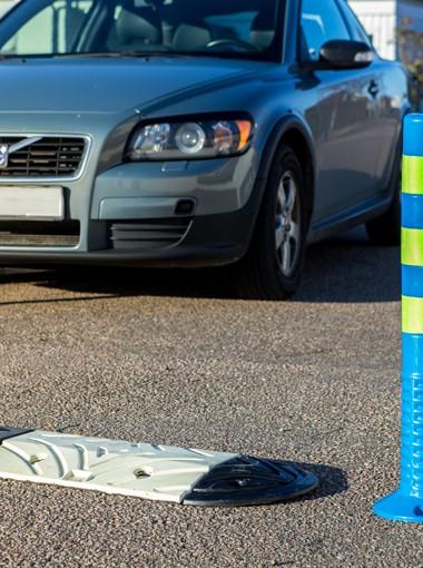 Bild av PP farthinder med Volvo i bakgrunden.